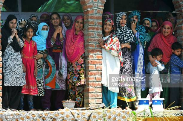 Kashmiri women watch the funeral procession of slain rebel Abid Ahmed in the village of Hajinar in the district Bandipora north of Srinagar on August...