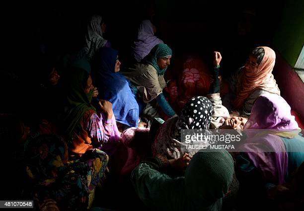 Kashmiri women weep as they mourn the death of a relative following flash floods triggered by heavy rainfall at Kullan village about 25 kms northeast...