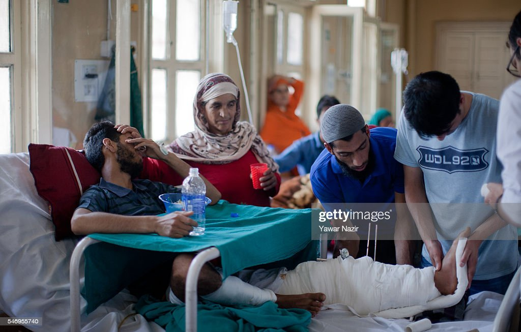 Kashmiri youth is being treated by a doctor as he lies wound in a hospital after a bullet of Indian government forces hit him during curfew after...