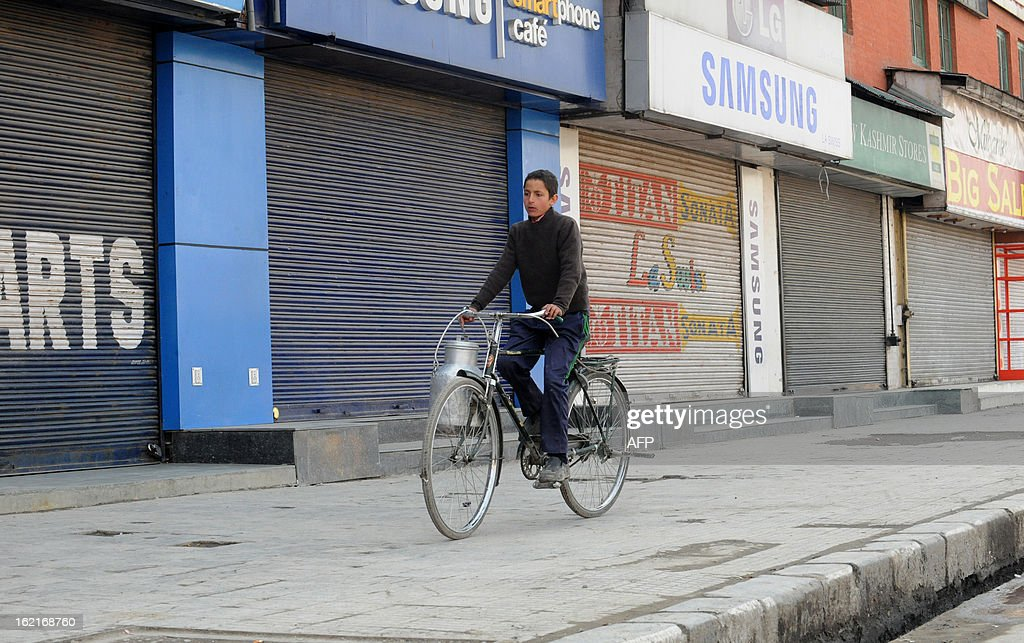 A Kashmiri youth rides a bicycle in front of closed shops during a shutdown in Srinagar on February 20, 2013. A separatist alliance, All Parties Hurriayt Conference, opposed to Indian rule in Kashmir called for a two-day strike in to press the demanded for return of Afzal Guru's mortal remains to his family. Guru was executed on February 9, 2013 and buried inside a high security prison in New Delhi after he was convicted of his role in a deadly attack on Indian parliament in 2001. AFP PHOTO/ Rouf BHAT