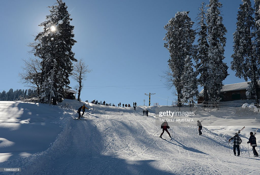 Kashmiri's and foreigners ski down a slope in Gulmarg, about 55 kms north of Srinagar, on December 31, 2012. Gulmarg is the main ski destination in Indian Kashmir and hundreds of foreigners visit the slopes despite an ongoing insurgency in the region. AFP PHOTO/ Tauseef MUSTAFA