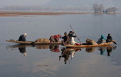 Kashmiris ferry people and goods in shikara boats on Dal lake on December 20 2013 in Srinagar the summer capital of Indian administered Kashmir India...