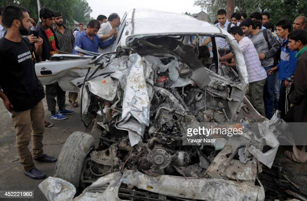 Kashmiris gather around a vehicle after it was hit by an Indian army truck killing at least six people July 16 2014 in Zaina Koot on the outskirts of...