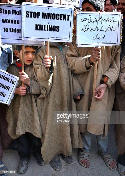 Kashmiris hold signs outside the main mosque to protest against a recent rise in human rights violations by Indian security forces February 27 2004...