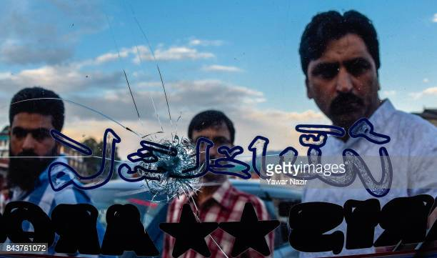 Kashmiris look towards a broken glass of a damaged vehicle after a grenade attack by suspected militants in a busy market on September 7 in Srinagar...