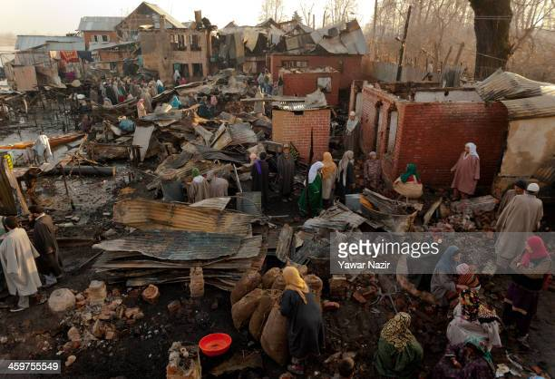 Kashmiris people salvage their belongings after a fire gutted many residential houses on December 30 in Srinagar the summer capital of Indian...