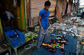 Kashmiris shopkeeper cleans silt from toy guns after the floods receded from the area on September 17 2014 in Srinagar the summer capital of Indian...