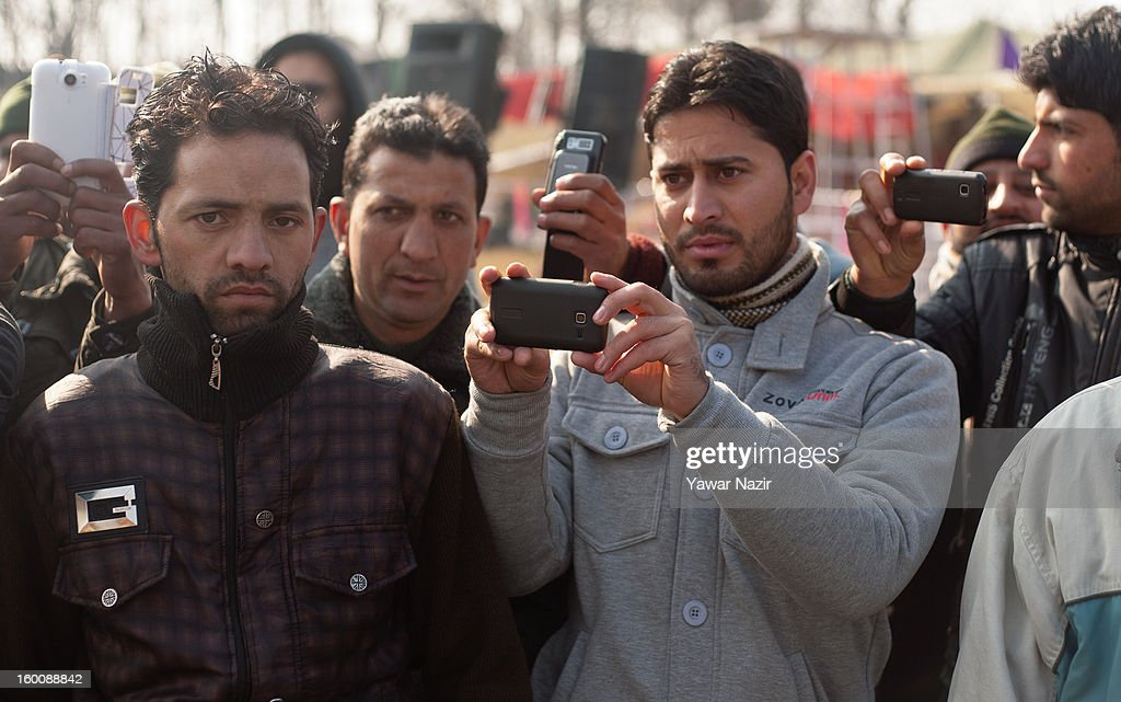 Kashmiris take pictures with their cell phones as they watch a main function at the Bakshi stadium during India's Republic Day celebrations on January 26, 2013 in Srinagar, the summer capital of Indian Administered Kashmir. All businesses, schools and shops were closed and traffic remained off the roads following a strike call given by Kashmiri separatist leaders against India's Republic Day celebrations in Kashmir. Meanwhile India deployed large numbers of Indian police and paramilitary forces to prevent any incidents during the official celebrations.