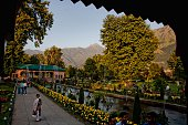 Kashmiris walk in the Shalimar garden a Mughal garden on the banks of Dal Lake and overlooked by the Zabarwan range built by the Mughal emperor...