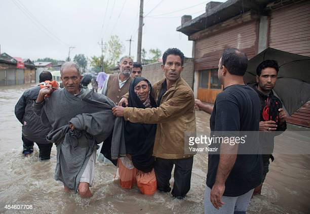 Kashmiris walk through a flooded area to a safer place on September 04 2014 in Srinagar the summer capital of Indian administered Kashmir India The...