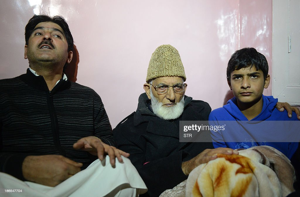 Kashmir's senior separatist leader, Syed Ali Shah Geelani (C) visits the house of Parliament attack convict Muhammed Afzal Guru, who was hanged earlier this year, to meet his son Galib (R) and brother Ajaz Ahmed Guru to express his soldiarity after addressing a public rally in his home town of Sopore, about 48 kms northwest of the capital Srinagar on November 1, 2013. Geelani formally launched a poll boycott campaign, asking people not to vote in the Jammu and Kashmir Assembly or Indian Parliamentary elections which are scheduled to take place in 2014. AFP PHOTO/Tauseef MUSTAFA