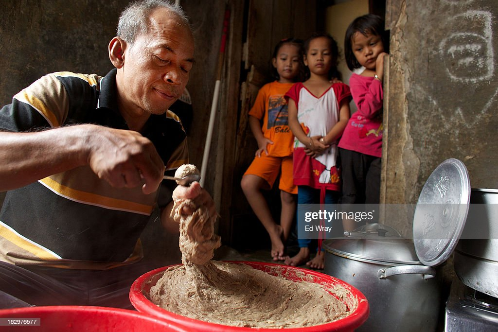Kasidi, a seller of a popular meatball noodle soup called bakso, makes his meatballs in his kitchen as his granddaughter and her friends watch on February 22, 2013 in Jakarta, Indonesia. The price of beef in Indonesia, now around Rp 95,000 (about USD 10) per kilo, has risen over the past 18 months due to strict import quotas for beef and live cattle which have also spawned a corruption scandal.