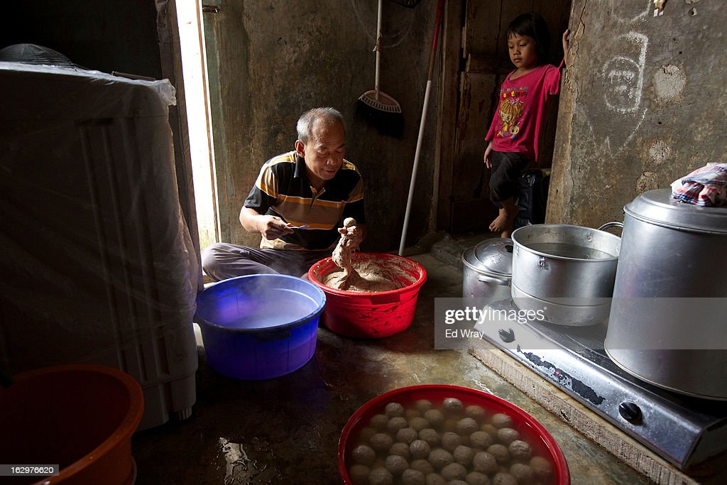 Kasidi, a seller of a popular meatball noodle soup called bakso, makes his meatballs in his kitchen, as his grand daughter watches on February 22, 2013 in Jakarta, Indonesia. The price of beef in Indonesia, now around Rp 95,000 (about USD 10) per kilo, has risen over the past 18 months due to strict import quotas for beef and live cattle which have also spawned a corruption scandal.