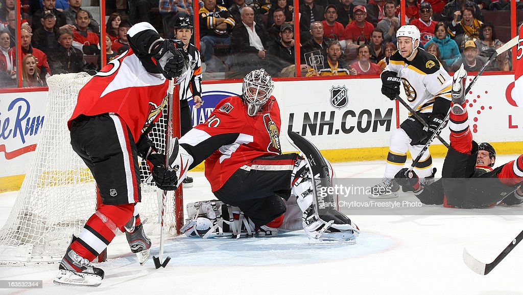 Kaspars Daugavins #23 of the Ottawa Senators makes a save on an open net as team mate <a gi-track='captionPersonalityLinkClicked' href=/galleries/search?phrase=Robin+Lehner&family=editorial&specificpeople=5894610 ng-click='$event.stopPropagation()'>Robin Lehner</a> #40 looks on, during an NHL game against the Boston Bruins, at Scotiabank Place, on March 11, 2013 in Ottawa, Ontario, Canada.