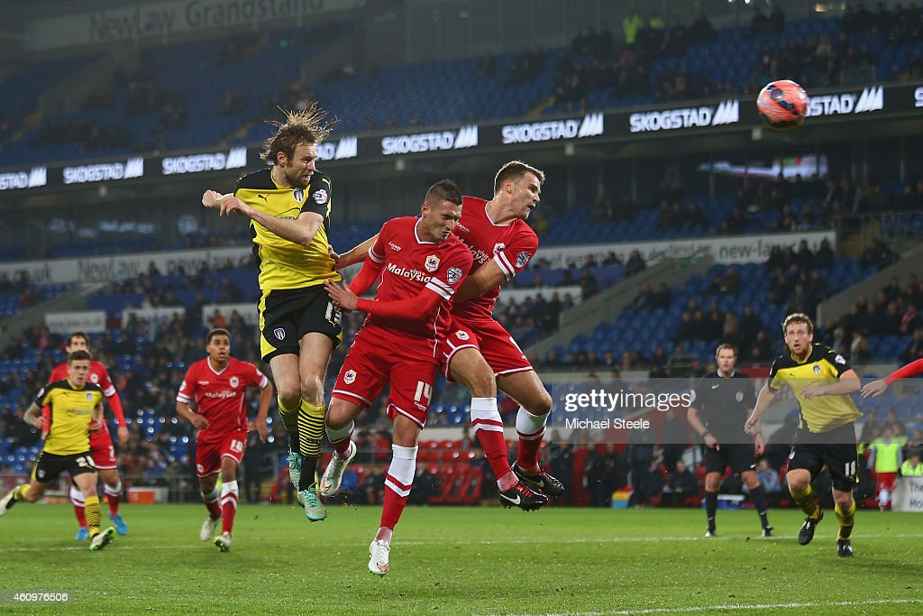 Kaspars Gorkss (L) of Colchester rises above Tom Adeyemi and Ben Turner of Cardiff only to narrowly miss during the FA Cup Third Round match between Cardiff City and Colchester United at Cardiff City Stadium on January 2, 2015 in Cardiff, Wales.