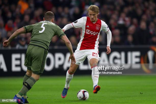 Kasper Dolberg of Ajax attempts to take the ball past Maciej Dabrowski of Legia Warszawa during the UEFA Europa League Round of 32 second leg match...