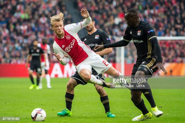 Kasper Dolberg of Amsterdam is attacked by Jeremy Morel and Nicolas Nkoulou of Lyon during the Uefa Europa League semi final first leg match between...