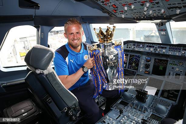Kasper Schmeichel holds the Premier League trophy onboard as the Leicester City squad set off on their preseason tour of America at Heathrow airport...