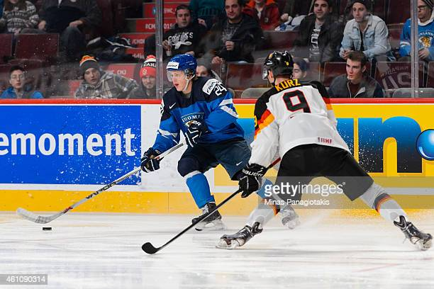 Kasperi Kapanen of Team Finland looks to play the puck as Patrick Kurz of Team Germany approaches in a preliminary round game during the 2015 IIHF...