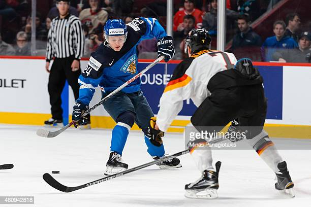 Kasperi Kapanen of Team Finland looks to play the puck near Dorian Saeftel of Team Germany in a preliminary round game during the 2015 IIHF World...