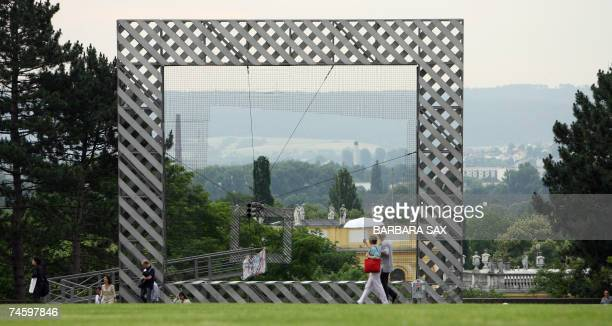 People walk past an art work framing the view on Kassel next to the documenta hall 14 June 2007 in Kassel central Germany during the documenta 12 art...