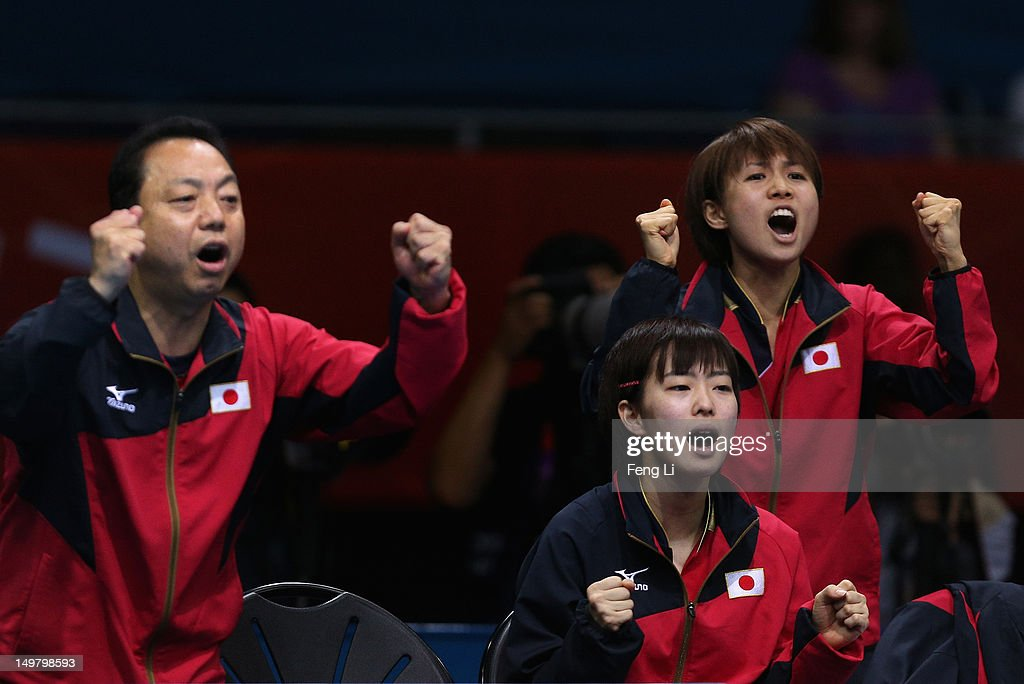 <a gi-track='captionPersonalityLinkClicked' href=/galleries/search?phrase=Kasumi+Ishikawa+-+Table+Tennis+Player&family=editorial&specificpeople=4946248 ng-click='$event.stopPropagation()'>Kasumi Ishikawa</a> (C)and <a gi-track='captionPersonalityLinkClicked' href=/galleries/search?phrase=Sayaka+Hirano&family=editorial&specificpeople=661037 ng-click='$event.stopPropagation()'>Sayaka Hirano</a> (L) of Japan celebrate with their coach Yasukazu Murakami (L) during Women's Team Table Tennis quarterfinal match against team of Germany on Day 8 of the London 2012 Olympic Games at ExCeL on August 4, 2012 in London, England.