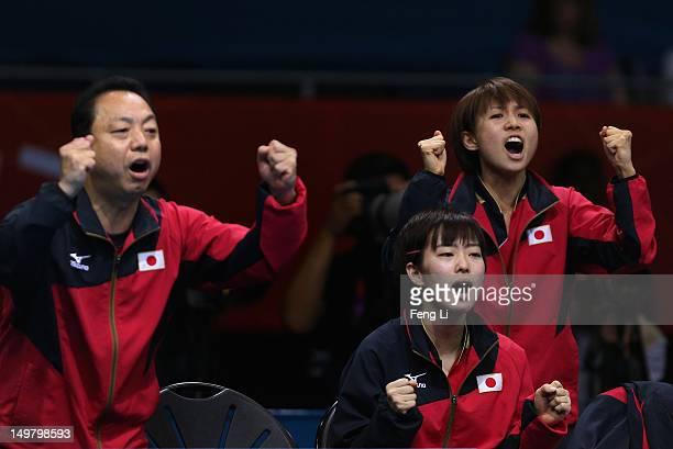 Kasumi Ishikawa and Sayaka Hirano of Japan celebrate with their coach Yasukazu Murakami during Women's Team Table Tennis quarterfinal match against...