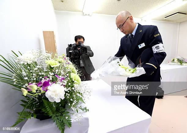 Kasumigaseki Area Station Master Mitsuaki Ota offers a flower bouquet at an altar for the victims at the Tokyo Metro Kasumigaseki Station on March 20...