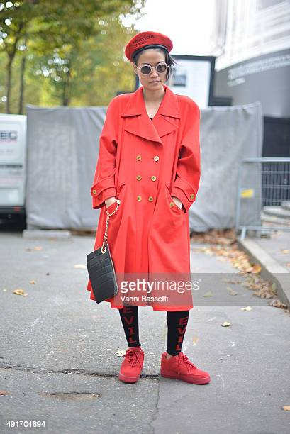 Kat Yeung poses wearing Chanel coat and clutch Nike shoes and Enfants Riches Deprimes hat before the Miu Miu show at the Palais de Iena during Paris...