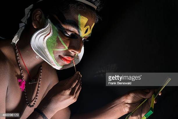 Katakali artist is applying the make up of the character Arjun for the play Santhana Gopalam