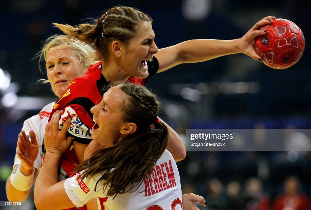Katarina Bulatovic of Montenegro (C) is challenged by Camilla Herrem (R) of Norway during the Women's European Handball Championship 2012 gold medal match between Norway and Montenegro at Arena Hall on December 16, 2012 in Belgrade, Serbia.