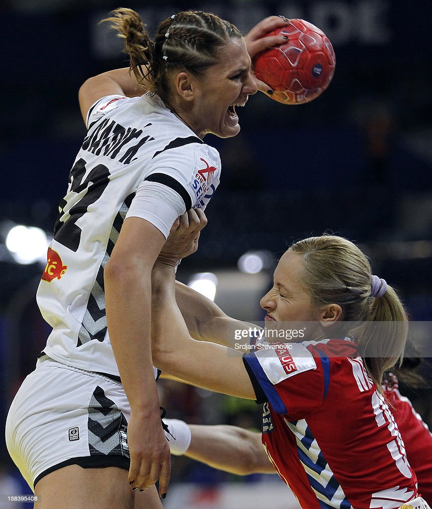 Katarina Bulatovic of Montenegro (L) is challenged by Jelena Nisavic (R) of Serbia during the Women's European Handball Championship 2012 semifinal match between Serbia and Montenegro at Arena Hall on December 15, 2012 in Belgrade, Serbia.