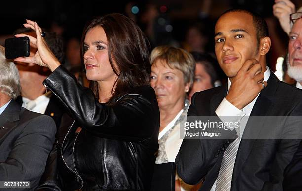 Katarina Witt takes pictures as Lewis Hamilton of Great Britain looks on during the MercedesBenz presentation of the SLS AMG at the international...