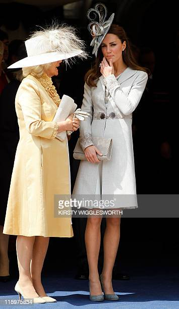Kate Duchess of Cambridge and the Duchess of Cornwall talk as they watch the procession at the Order of the Garter Service at St George's Chapel in...