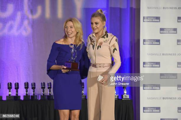 Kate Herman President and Publisher of Nashville Business Journal Women in Music City and Kelsea Ballerini take photos onstage at the 2017 Nashville...