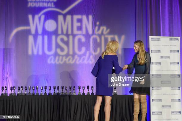 Kate Herman President and Publisher of Nashville Business Journal Women in Music City and Beville Dunkerley of Pandora take photos onstage at the...