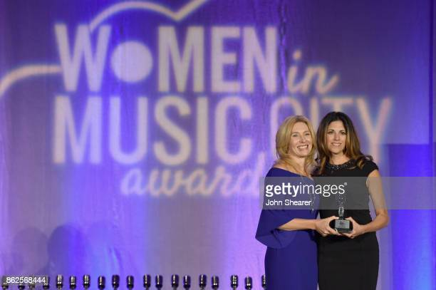 Kate Herman President and Publisher of Nashville Business Journal Women in Music City and Kerri Edwards of KP Entertainment take photos onstage at...