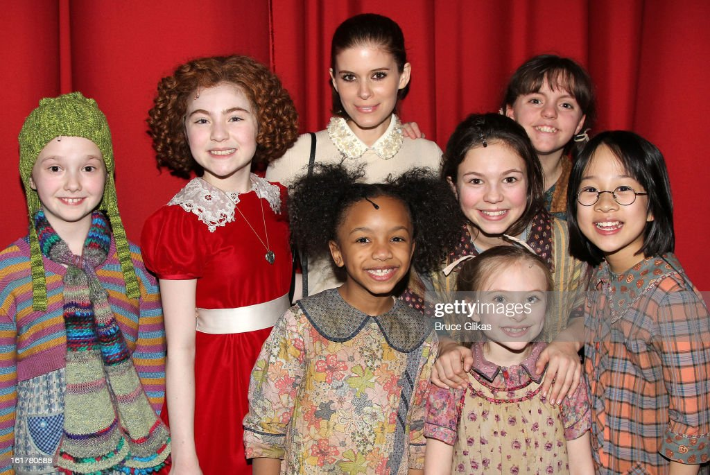 Kate Mara poses with 'Annie' and The Orphans backstage at the hit musical 'Annie' on Broadway at The Palace Theater on February 15 2013 in New York...