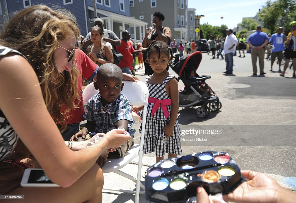 Kate Rust, an intern with the Dorchester Bay Economic Development Corporation, left, paints a Superman logo on the arm of 3-year-old Tykell Gill during a block party on Hendry Street in Dorchester, June 15, 2013. Behind Gill is Melissa Silva-Mendes, 3. The neighborhood has been the focus of a concerted effort between the City of Boston, the Boston Police Department, Dorchester Bay Economic Development Corporation, 4 Streets Crime Watch, and the neighborhood all worked together to better this community.