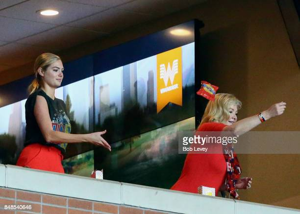 Kate Upton left tosses a bag of peanuts to the crowd at Minute Maid Park on September 17 2017 in Houston Texas