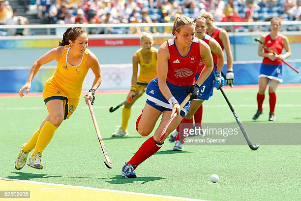 Kate Walsh of Great Britain dribbles against the defense of Hope Munro of Australia during the women's classification hockey match at the Olympic...