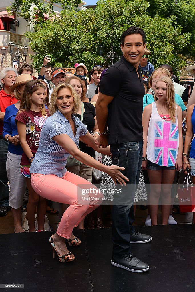 Katee Sackoff (L) attempts to place handcuffs on <a gi-track='captionPersonalityLinkClicked' href=/galleries/search?phrase=Mario+Lopez&family=editorial&specificpeople=235992 ng-click='$event.stopPropagation()'>Mario Lopez</a> at 'Extra' at The Grove on July 25, 2012 in Los Angeles, California.