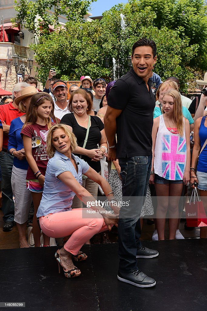 Katee Sackoff (L) attempts to place handcuffs on Mario Lopez at 'Extra' at The Grove on July 25, 2012 in Los Angeles, California.