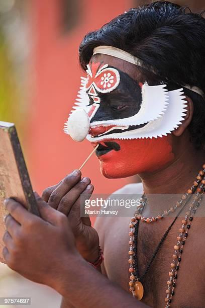 Kathakali dance performer doing make-up