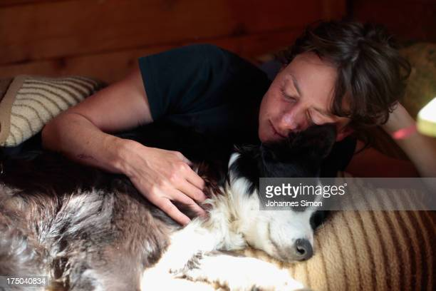 Katharina Brueggebors relaxes with sheepdog Nelly on July 28 2013 inside her cottage at the Sesvenna Alpe near Malles Venosta/Mals Italy As...
