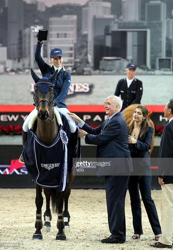 Katharina Offel (L) of Ukraine holds the trophy after winning the Longines Speed Challenge during the Longines Hong Kong Masters International Show Jumping at Asia World Expo on February 28, 2013 in Hong Kong, Hong Kong.