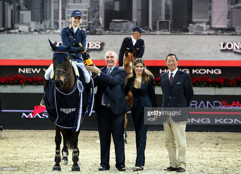 Katharina Offel (L) of Ukraine receices a bottle of champagne from Longines President Walter Von Kanel (2nd L) after winning the Longines Speed Challenge during the Longines Hong Kong Masters International Show Jumping at Asia World Expo on February 28, 2013 in Hong Kong, Hong Kong.