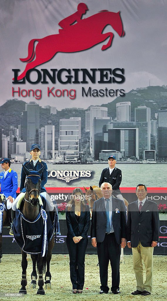 Katharina Offel (L) of Ukraine riding Olivia de Nantuel and President of Longines, Walter Von Kanel (R) stand with dignitaries for the Ukrainian national anthem during the Furusiyya FEI Nations Cup on February 28, 2013 in Hong Kong.