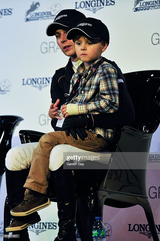Katharina Offel of Ukraine sits with a child on the winners podium during the Furusiyya FEI Nations Cup on February 28, 2013 in Hong Kong.