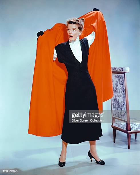 Katharine Hepburn US actress wearing a black dress as she puts on a red coat in a studio portrait against a white background 1965